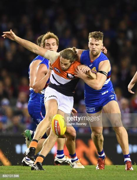 Callan Ward of the Giants kicks whilst being tackled by Jake Stringer of the Bulldogs during the round 21 AFL match between the Western Bulldogs and...