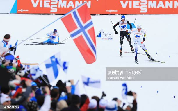 Calle Halfvarsson of Sweden and Curdin Perl of Switzerland head for the finish line as Matti Heikkinen of Finland crashes in the Men's 4x10km Cross...