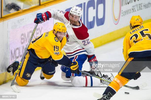 Calle Jarnkrok of the Nashville Predators and Karl Alzner of the Montreal Canadiens go after the puck during an NHL game at Bridgestone Arena on...