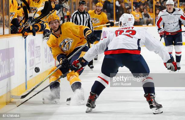 Calle Jarnkrok of the Nashville Predators dumps the puck in the zone against Madison Bowey of the Washington Capitals during an NHL game at...