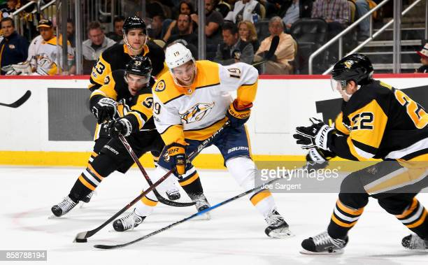 Calle Jarnkrok of the Nashville Predators handles the puck against Greg McKegg of the Pittsburgh Penguins at PPG Paints Arena on October 7 2017 in...