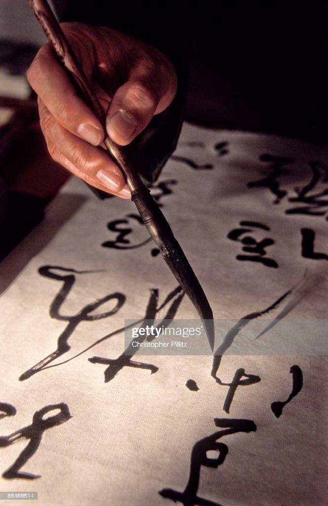Calligrapher delicately works his art
