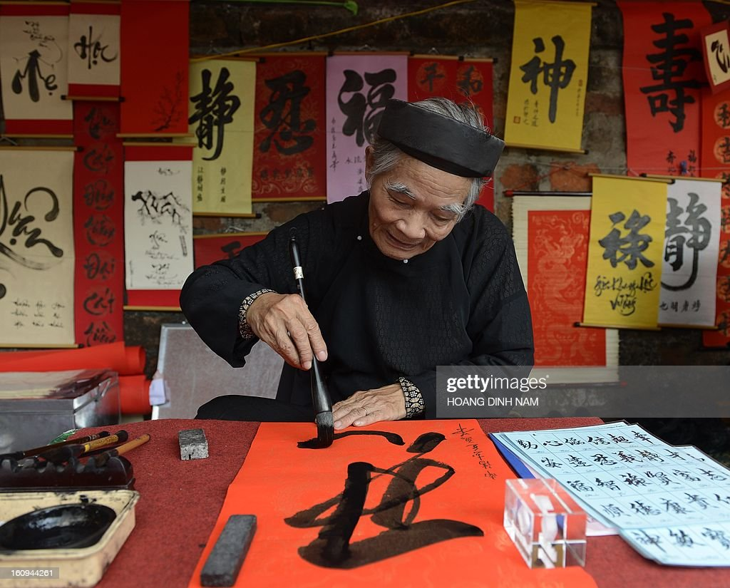 A calligrapher writes down best wishes for the lunar new year or Tet in Vietnamese, for customers outside the Temple of Literature in downtown Hanoi on February 8, 2013. Vietnamese will have from this week-end a nine-day long Tet holiday, the longest ever lunar new year holiday provided by the Vietnamese government. AFP PHOTO/HOANG DINH Nam
