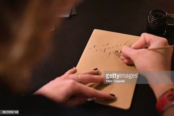 A calligrapher writes Shakespeare quotes on notebooks during TNT's Season One 'Will' Premiere After Party at Bryant Park on June 27 2017 in New York...