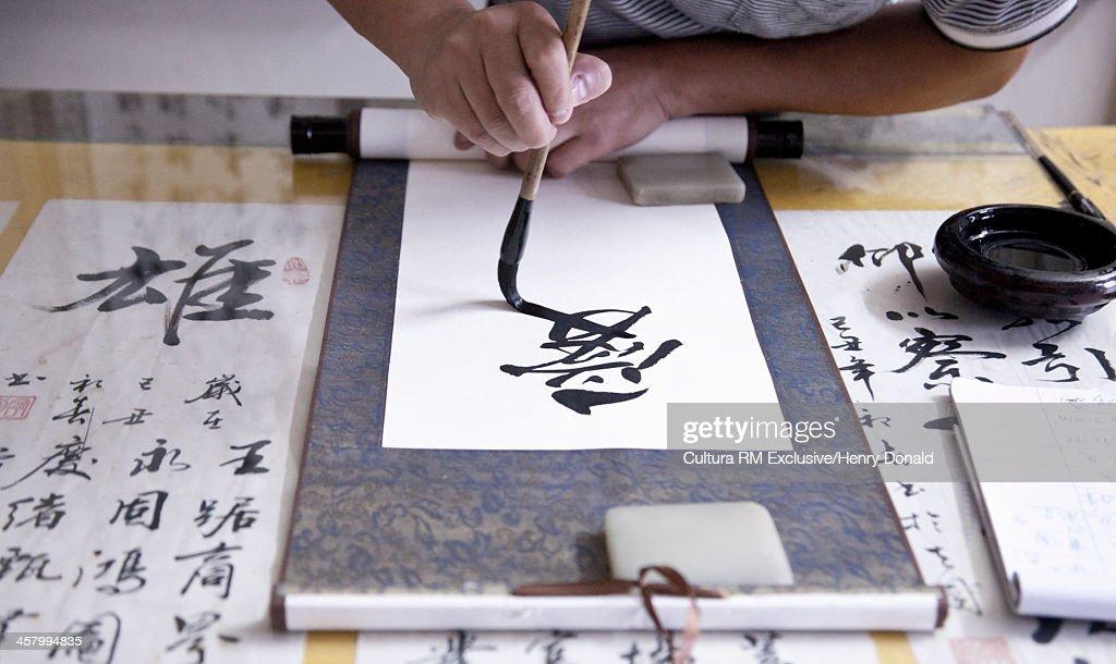 Calligrapher writing Chinese symbols on scroll