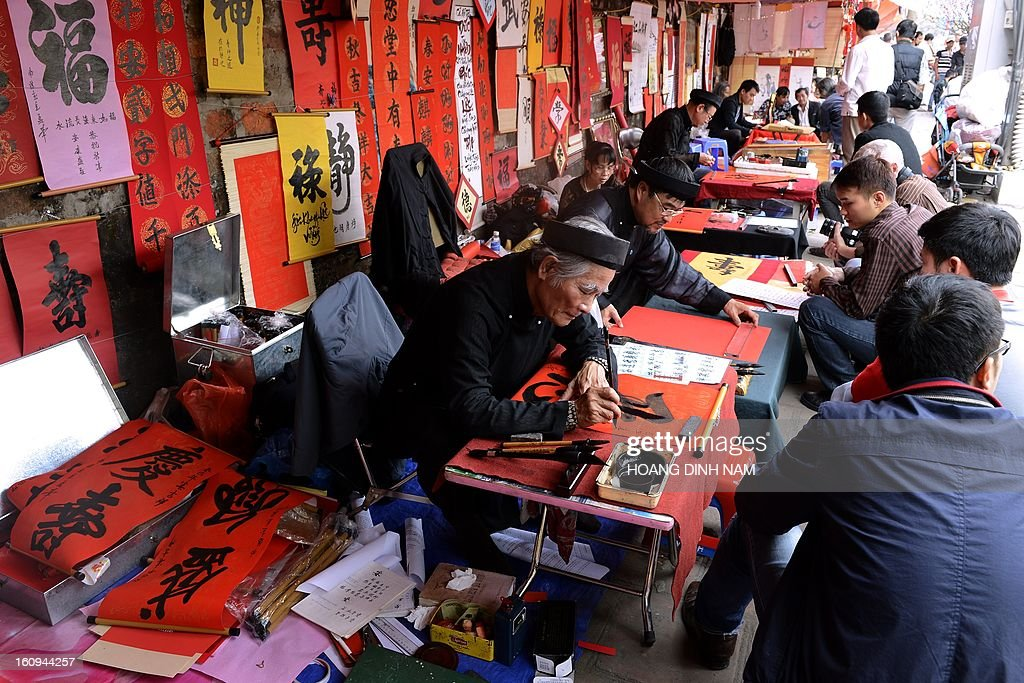 Calligraphers (L) write down best wishes for the lunar new year or Tet in Vietnamese, for customers (R) outside the Temple of Literature in downtown Hanoi on February 8, 2013. Vietnamese will have from this week-end a nine-day long Tet holiday, the longest ever lunar new year holiday provided by the Vietnamese government. AFP PHOTO/HOANG DINH Nam