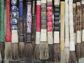 A row of calligraphy brushes (or paintbrushes) hangs in a line in an art market in Shanghai, China.