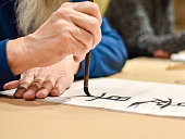 Calligraphy master drawing chinese hieroglyph with a brush