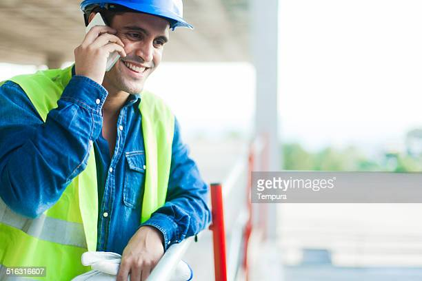 Calling with smart phone at construction site.
