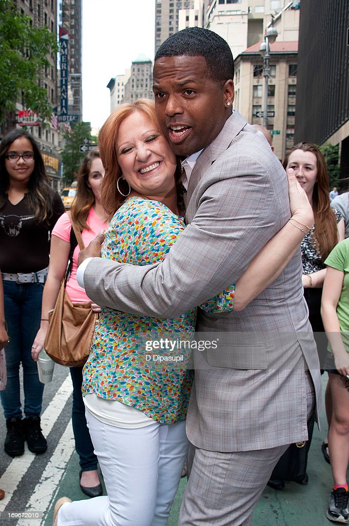 AJ Calloway (R) hugs Caroline Manzo of 'Real Housewives of New Jersey' during her visit to 'Extra' in Times Square on May 30, 2013 in New York City.