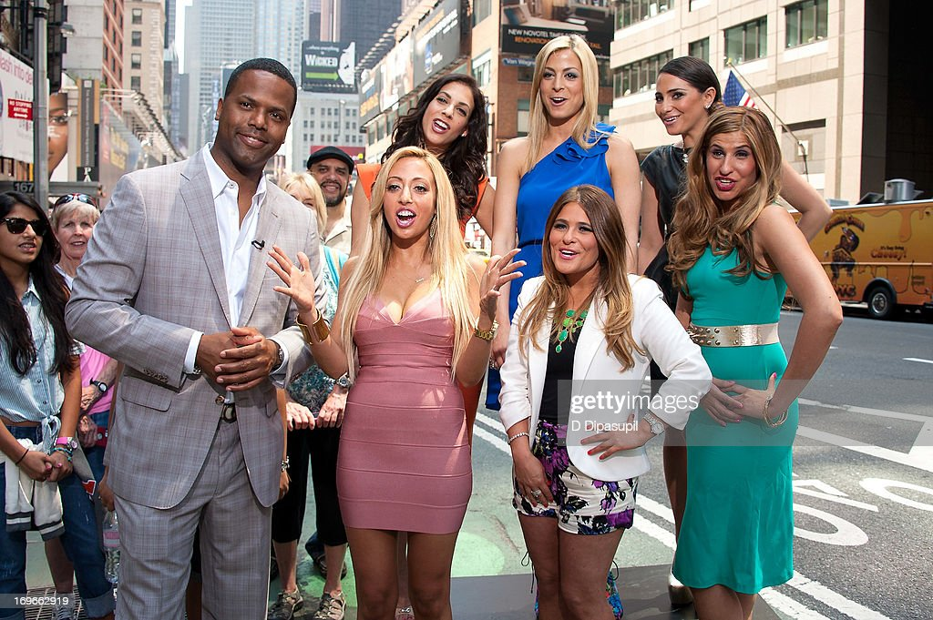 AJ Calloway (L) interviews (L-R rear) Joey Lauren, Casey Cohen, Erica Gimbel, (L-R front) Amanda Bertoncini, Ashlee White, and Chanel 'Coco' Omari of 'The Princesses Of Long Island' during their visit to 'Extra' in Times Square on May 30, 2013 in New York City.