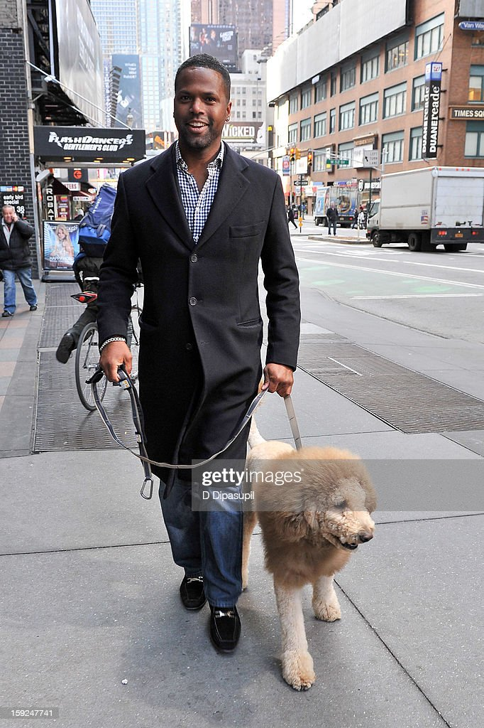 AJ Calloway walks Charles the Monarch during a taping of 'Extra' in Times Square on January 10, 2013 in New York City.