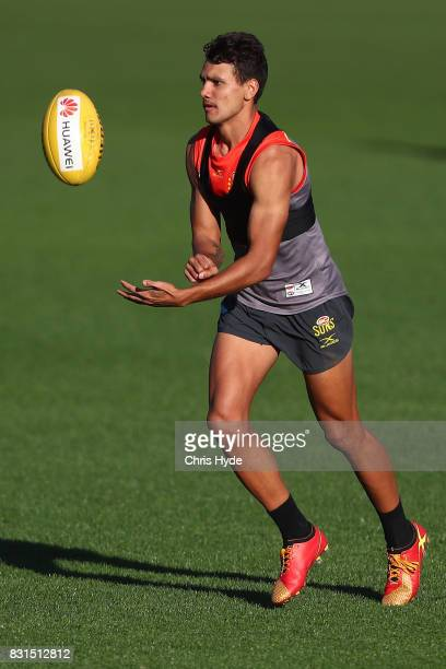 Callum Ah Chee handballs during a Gold Coast Suns AFL training session at Metricon Stadium on August 15 2017 in Gold Coast Australia
