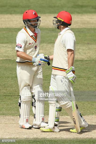 Callum Ferguson of South Australia celebrates his half century with Jake Lehmann during day three of the Sheffield Shield match between Victoria and...
