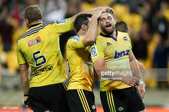 Callum Gibbins of the Hurricanes is congratulated on his try by teammates James Marshall and Brad Shields during the round seven Super Rugby match...