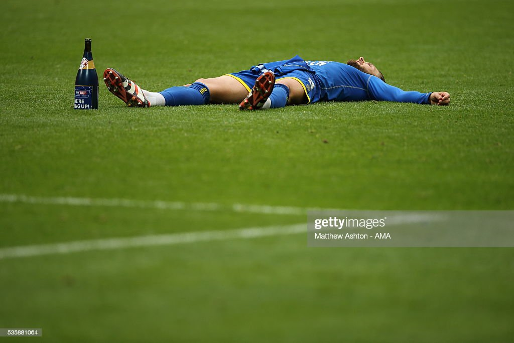 Callum Kennedy of AFC Wimbledon takes a time out on the pitch as he celebrates promotion after victory in the Sky Bet League Two Play Off Final between Plymouth Argyle and AFC Wimbledon at Wembley Stadium on May 30, 2016 in London, England.