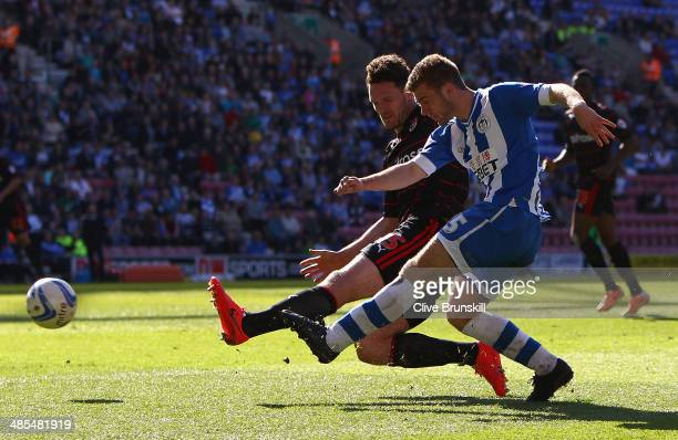 Callum McManaman of Wigan Athletic shoots at goal past Sean Morrison of Reading during the Sky Bet Championship match between Wigan Athletic and...