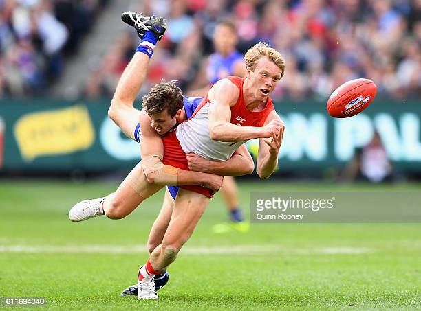 Callum Mills of the Swans handballs whilst being tackled by Zaine Cordy of the Bulldogs during the 2016 AFL Grand Final match between the Sydney...