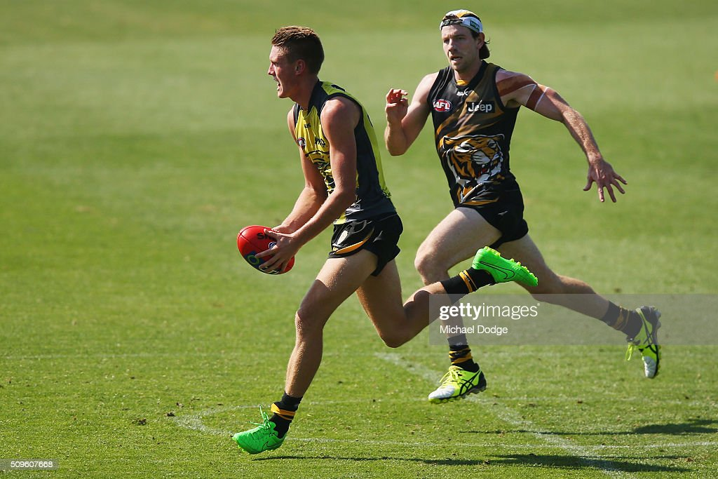Callum Moore of the Tigers runs with the ball away from Jake Batchelor of the Tigers during the Richmond Tigers AFL intra-club match at Punt Road Oval on February 12, 2016 in Melbourne, Australia.