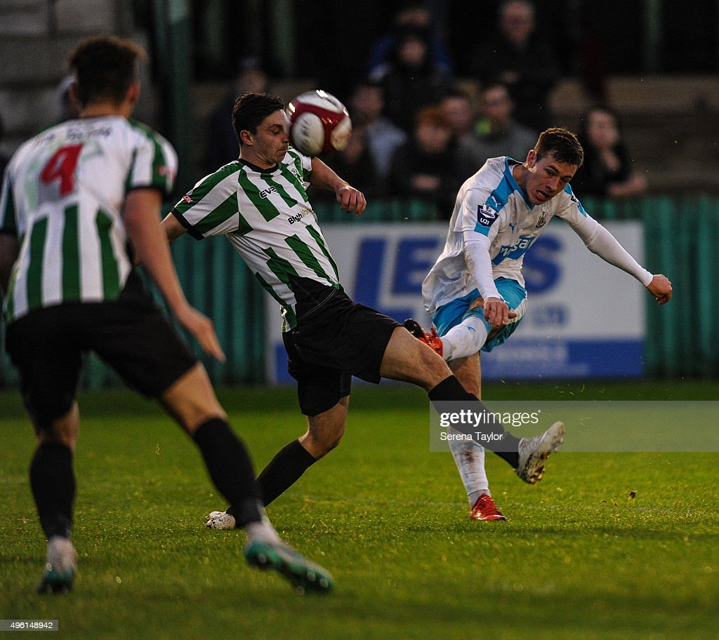 Callum Roberts (R) of of Newcastle strikes the ball during The Northumberland Senior Cup match between Blyth Spartans and Newcastle United at Croft Park on November 7, 2015, in Blyth, England.