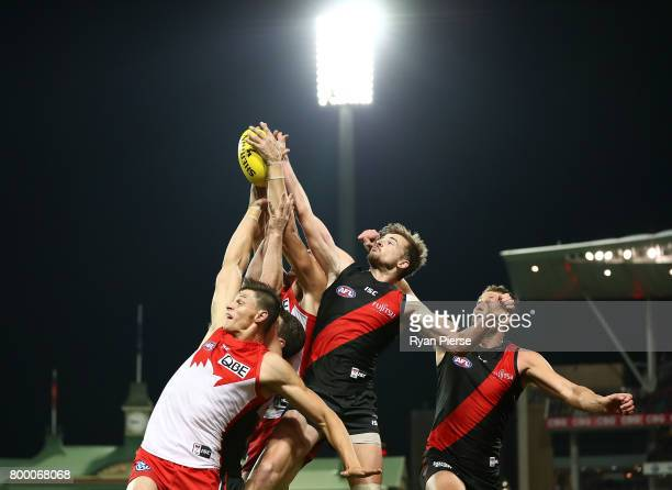 Callum Sinclair of the Swans competes for the ball against Martin Gleeson and Tom Bellchambers of the Bombers during the round 14 AFL match between...