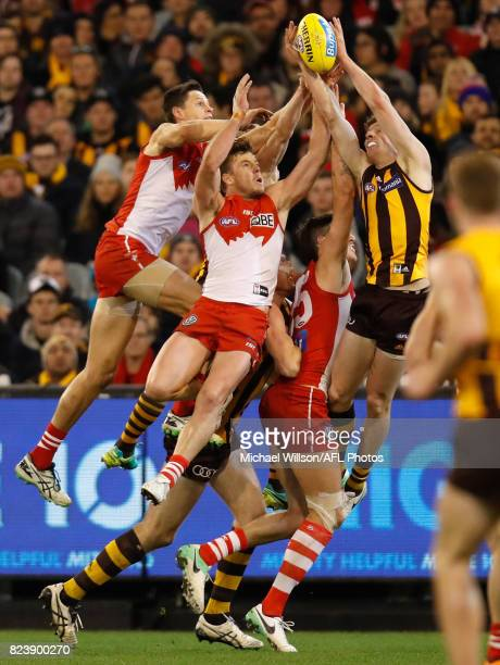 Callum Sinclair of the Swans Luke Parker of the Swans and Tim O'Brien of the Hawks compete for the ball during the 2017 AFL round 19 match between...