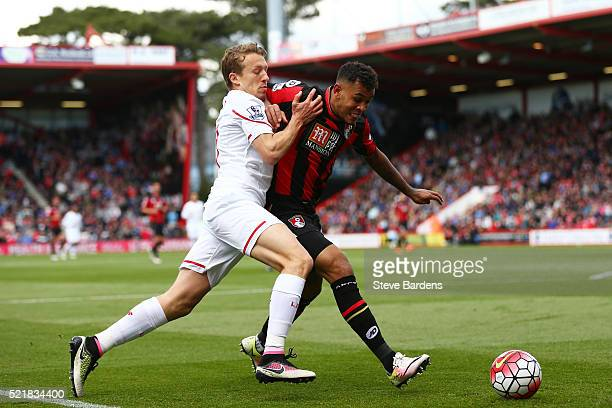 Callum Wilson of Bournemouth holds off pressure from Lucas Leiva of Liverpool during the Barclays Premier League match between AFC Bournemouth and...