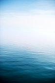 High contrast image of small ripples and waves of a calm, deep lake with foggy horizon