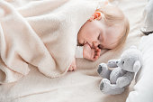 Tranquil infant dreaming in the morning on cozy sofa wrapped in soft covering. Teddy bear is on bed