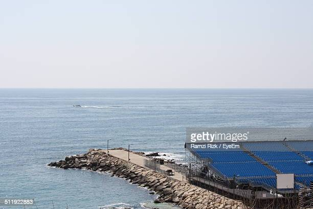 Calm blue sea against clear sky with solar panels in foreground