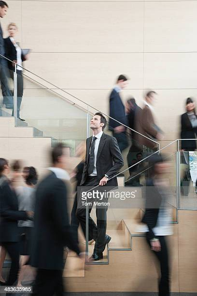 Calm businessman in busy office staircase