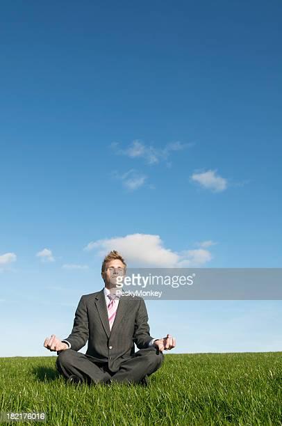 Empresario Meditando frescos al aire libre en prado vacío