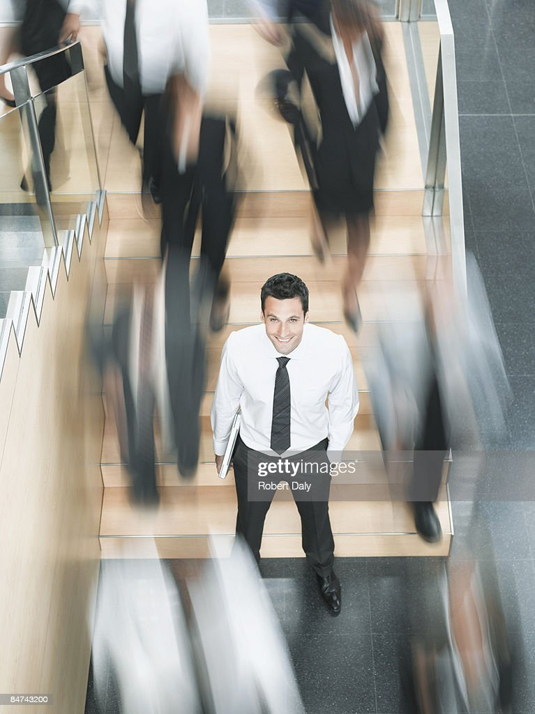 Calm businessman standing in busy office : Stock Photo