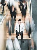 Calm businessman standing in busy office