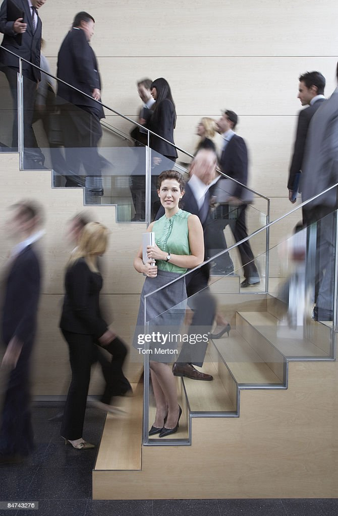 Calm businesswoman in busy office staircase : Stock Photo