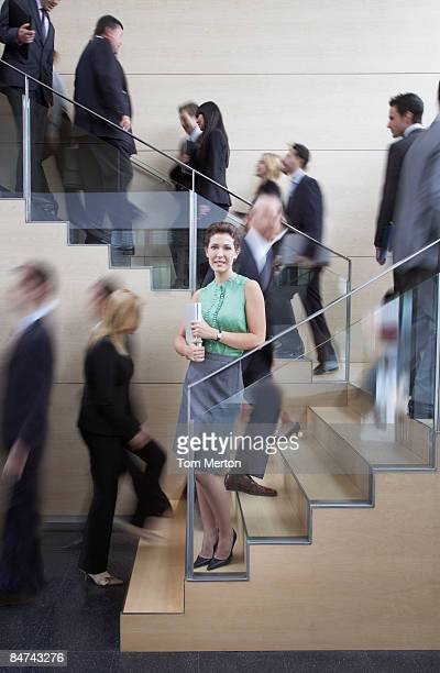 Calm businesswoman in busy office staircase