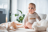 Low angle portrait of plump baby sitting on bedding and playing with toy. Copy space in left side