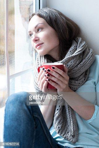 Calm dreamy woman leaning on the window glass : Foto de stock