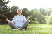 Peace and relaxation. Calm nice peaceful woman sitting on the grass and closing her eyes while meditating
