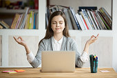 Calm woman relaxing meditating with laptop, no stress free relief at work concept, mindful peaceful young businesswoman or student practicing breathing yoga exercises at workplace, office meditation