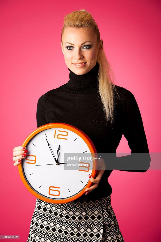 Calm smiling woman with big orange clock gesturing no rush : Bildbanksbilder