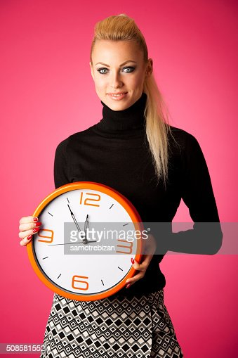 Calm smiling woman with big orange clock gesturing no rush : Stock Photo