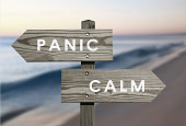 Calm vs Panic signs with blurred beach background