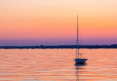 Orange and pink skies are reflected in very calm seas in Dorset, UK. A small sailing boat bobs in the middle distance