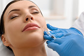 Close up serene girl lying in surgery room during botox procedure