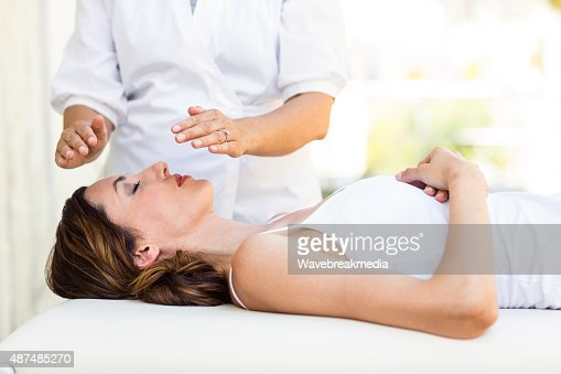 http://media.gettyimages.com/photos/calm-woman-receiving-reiki-treatment-picture-id487485270?s=170667a&w=1007