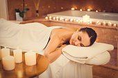 This is the real pleasure. Voluptuous girl is sleeping on massage table at spa. Candles create romantic atmosphere
