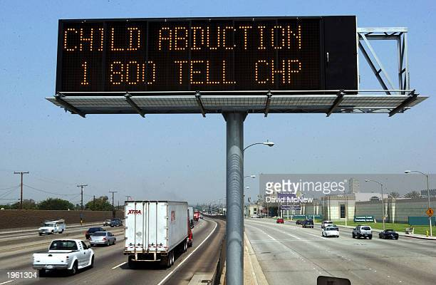 A Caltrans freeway sign over Interstate 5 flashes 'child abduction 1 800 TELL CHP' in addition to the description of a suspect's vehicle as part part...