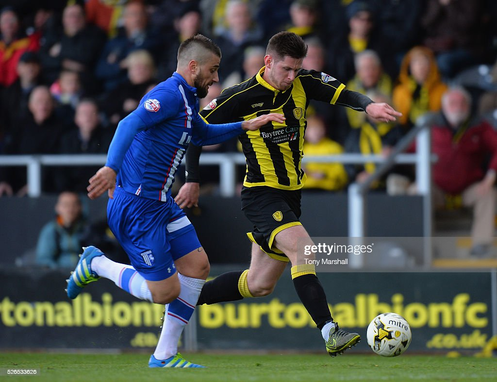 Calum Butcher of Burton Albion is tackled by Max Ehmer of Gillingham during the Sky Bet League One match between Burton Albion and Gillingham at Pirelli Stadium on April 30, 2016 in Burton-upon-Trent, England.