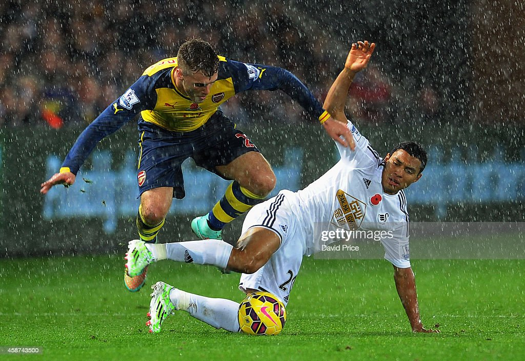 Calum Chambers of Arsenal skips over Jefferson Montero of Swansea during the match between Swansea and Arsenal in the Barclays Premier League at Liberty Stadium on November 9, 2014 in Swansea, Wales.
